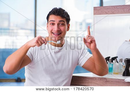 Handsome man brushing teeth in the morning