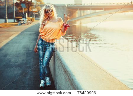Young cool teenage style woman standing on stone quay at morning sunrise
