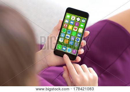 woman in purple dress holding touch phone with home screen icons apps