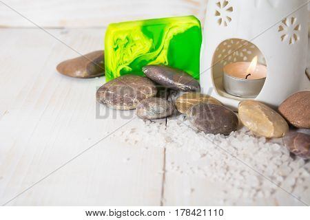 Spa still life with salt stone and green soap with aroma lamp on the white wooden background with copy space