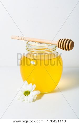 Light honey in the jar with spoon and flower on the white background