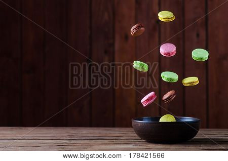 Macaroons Multicolored Falls Into A Clay Bowl On A Wooden Table.