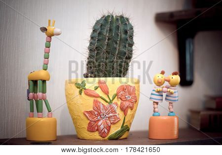 Old colorful wooden toy giraffe and Chicks are standing next to a prickly cactus in a yellow clay pot
