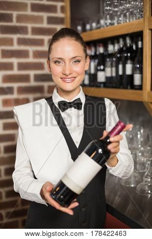 Beautiful barmaid holding a bottle of red wine