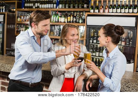 Attractive friends toasting with beverages in a bar