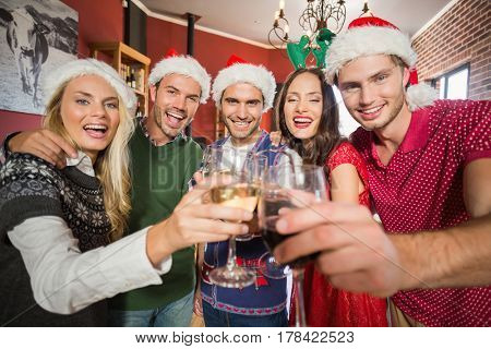 Friends wearing Christmas hats toasting in a bar