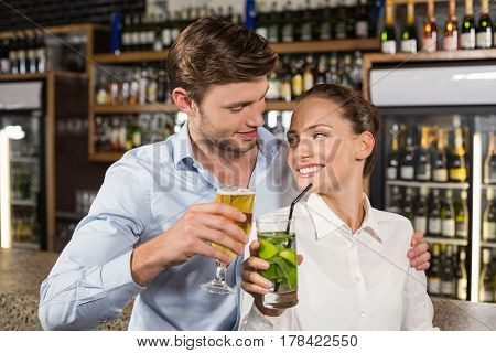 Attractive man and woman hugging and looking at each other while holding beverages