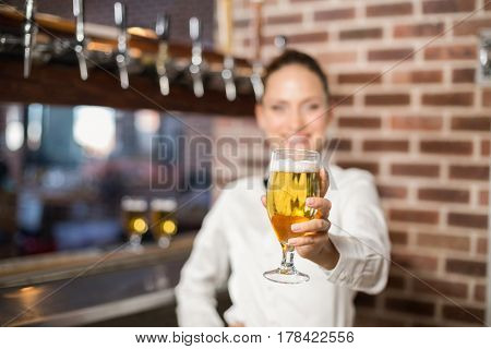 Beautiful barmaid holding a pint of beer in a bar