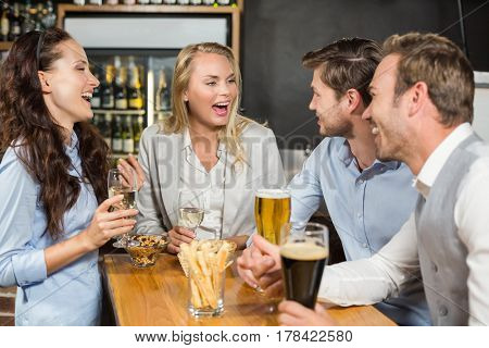 Attractive friends talking around the table in the bar