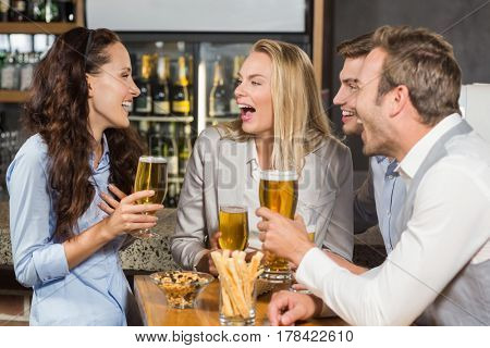 Attractive friends laughing while drinking beer at a bar