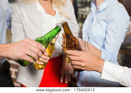 Close up attractive friends toasting with bottles of beer in a bar