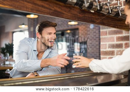 Beautiful barmaid giving handsome man his order