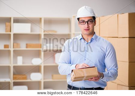 Young worker in the postal office dealing with parcels