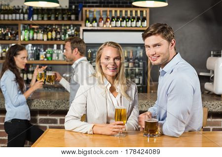 Attractive couples holding beers with one couple talking and the other smiling at camera