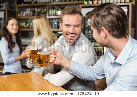 Handsome men toasting in front while talk behind in a bar