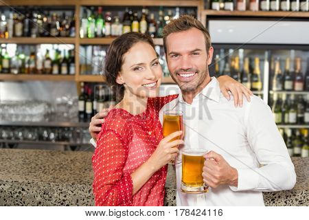 Smiling attractive couple holding beers while hugging