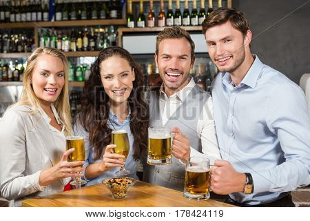 Attractive friends toasting with beer while looking at camera in a bar