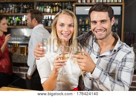 Attractive couple smiling at camera while toasting with white wine