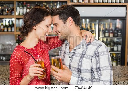 Attractive couple head to head smiling with beers in hand