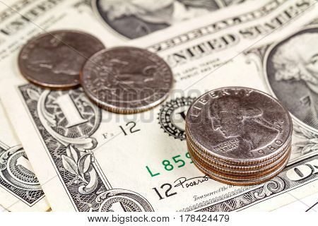 Coins on the background of US dollars banknotes. Focus in the foreground