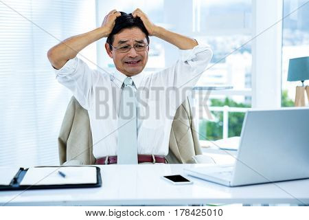 Overwhelmed asian businessman going crazy in office