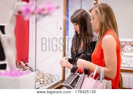 Two beautiful women with shopping bags looking at a display of watches in shop