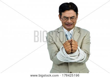 Asian businessman tied up in rope on white background
