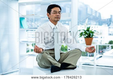 Concentrated asian businessman relaxing in office