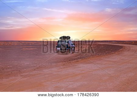 Driving through the Sahara desert in Morocco at sunset