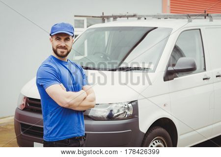 Man standing with arms crossed in front of his van