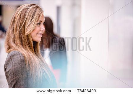 Beautiful woman window shopping outside a shop in mall