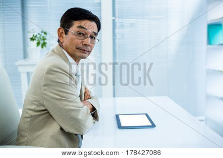 Serious businessman using tablet in office