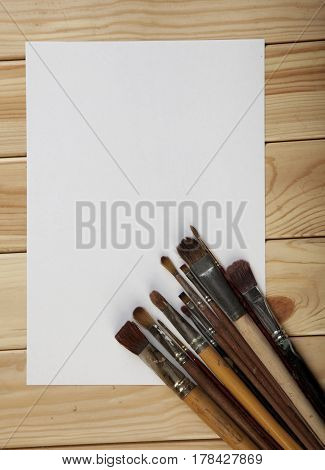 Brushes And Empty White  Paper On A Wooden Table