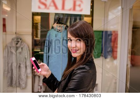 Beautiful woman using her phone while window shopping in front of sale window