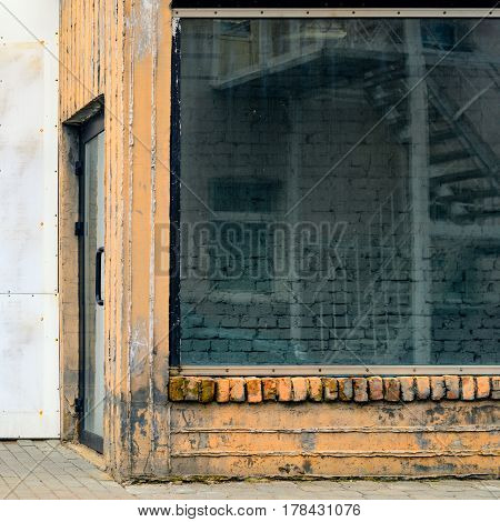 Abandoned storefront. Empty old showcase. Building entry
