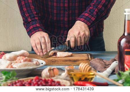 Preparation healthy food. Man cooking chicken wings with cranberry sauce in a home kitchen