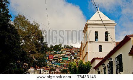 Slums in the El Hatillo district of Caracas rise on a hill behind a church