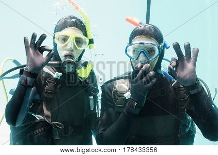 Couple on scuba training in swimming pool showing ok gesture