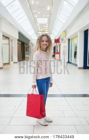 Happy girl holding a shopping bag in shopping mall