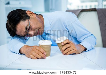 Businessman with two cup of coffee in office