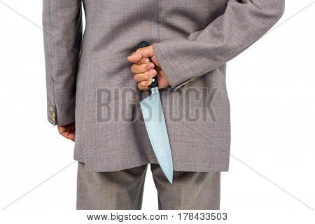 Businessman holding knife behind his back on white background