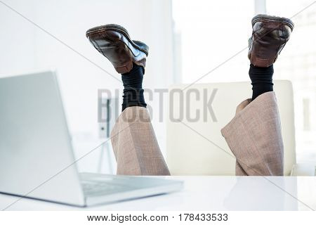 Businessman lying on the ground with feet up in office