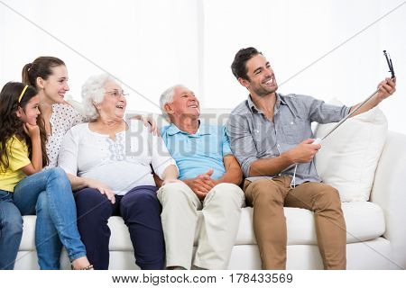 Smiling family taking self portrait while sitting on sofa at home
