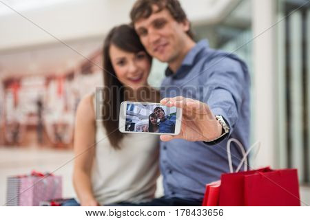 Happy couple taking a selfie in shopping mall