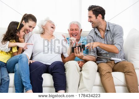 Family laughing while looking at smartphone photos at home
