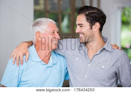 Smiling father and son with arm around wile standing at home