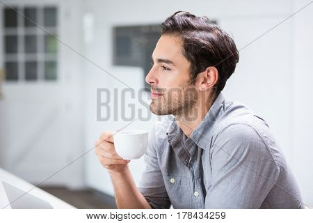 Thoughtful young man holding coffee cup at home