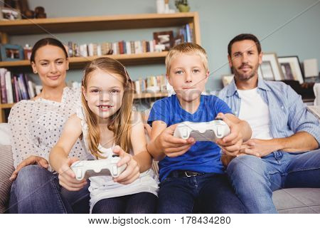 Smiling siblings playing video games with parents at home