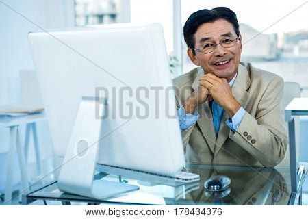 Smiling asian businessman working on computer in office