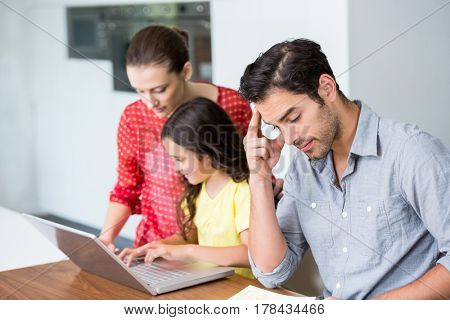 Daughter and mother working on laptop with tensed father sitting at desk in home